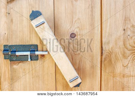 wooden handle on a wooden door with metal latch closeup