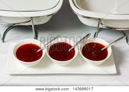 Three plates with red meat sauce and spoons are on a white glass pedestal.