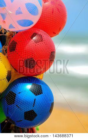 Kids Air balls deisgned as soccer balls on Sri Lankan beach with ocean on background. Beach fun