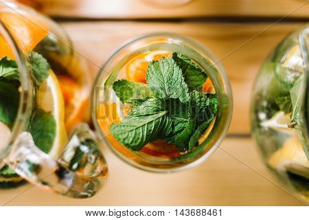 Cocktail with orange and mint top view, macro. Standing on a wooden table, without the liquid only ingredients.