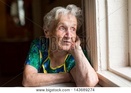 Grandma looks out the window. Old age, loneliness.