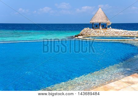 Tropical scenery with seaside infinitty swimming pool at Maldivian resort and view to blue ocean