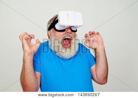 Aged bearded man in 3D virtual reality glasses is freaked out while testing virtual reality technology isolated against white background