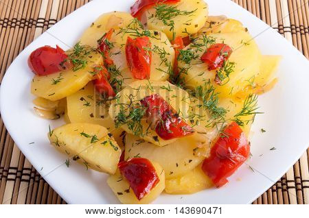 Vegetarian dish with organic vegetables - slices of stewed potatoes and vegetable seasonings on a wooden background
