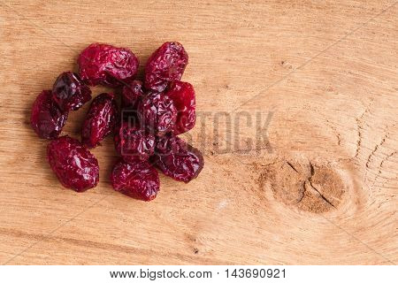 Healthy food organic nutrition. Heap of dried cranberries cranberry fruit on wooden table background
