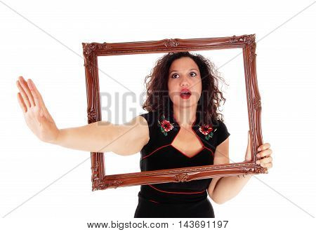 A angry woman looking trough a picture frame stretching one hand out say NO isolated for white background.