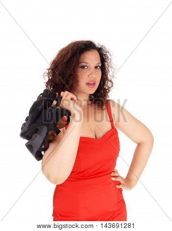 A pretty woman in a red dress standing isolated for white background holding her black shoes over her shoulder.