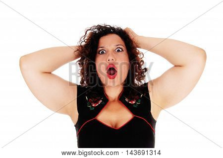 A beautiful young woman in a black dress with her hands behind her head screaming with open mouth isolated for white background.