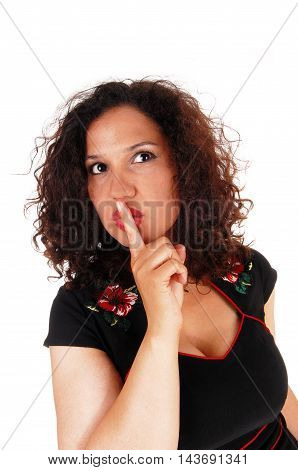 A lovely young woman with curly brunette hair in closeup holding one finger over her mouth isolated for white background.