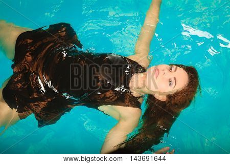 Woman dreaming relaxing in swimming pool water. Young girl wearing black dress floating.