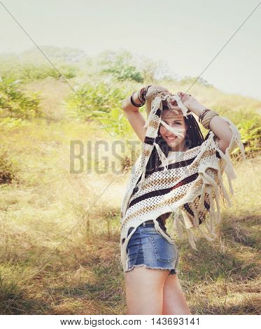 Happy boho style woman dressed in knitted poncho, jeans shorts and headband posing hands up against sunny autumn park, vintage colors, space for text