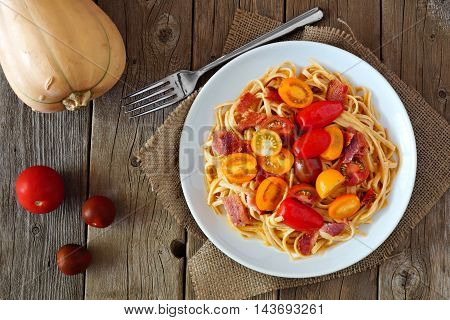 Creamy Butternut Squash Pasta Dish With Bacon And Cherry Tomatoes, Above View On Rustic Wood