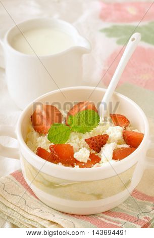 Breakfast with farmer cottage cheese, strawberries and mint, on white background