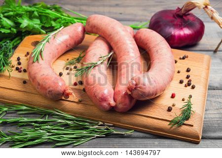 Raw meat is not cooked sausages for grilling seasoning for sausages onions dill parsley rosemary pepper board gray wooden background. Thuringian sausages