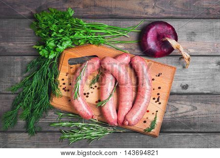 Raw meat is not cooked sausages for grilling seasoning for sausages onions dill parsley rosemary pepper board gray wooden background. Thuringian sausages. Top view.
