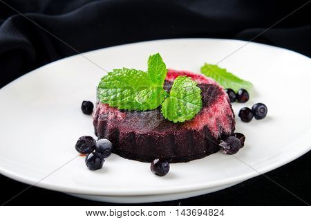 Homemade refreshing organic blueberry sorbet on a white plate with mint, on black background
