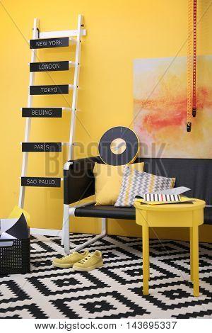 Stylish room interior on yellow wall background
