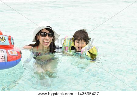 mother and son playing at pool during summer vacation