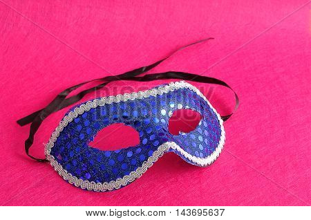 A carnival mask displayed on a pink background