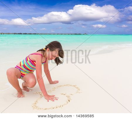 Girl drawing heart on sand