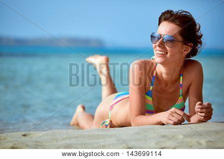 beautiful sexy woman dressed in bikini lying on the beach