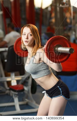 Concept: sport, healthy lifestyle. Young strong girl do squats with a barbell