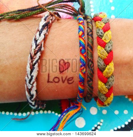 a heart drawn on a arm with bracelets of colors
