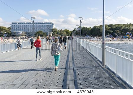 KOLOBRZEG - AUGUST 15: Tourists enjoy the sunny weather and walk along the pier on 15 August 2016 in Kolobrzeg, Poland.