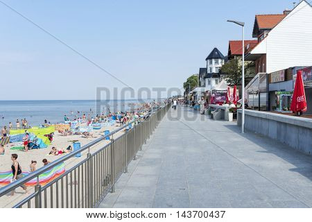 SARBINOWO - AUGUST 20: Tourists enjoy the sunny weather and relaxing on the Baltic sea beach at the promenade on 20 August 2016 in Sarbinowo, Poland.