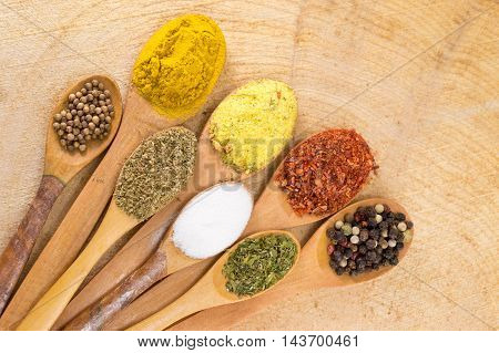Spices In Wooden Spoons On Wooden Table
