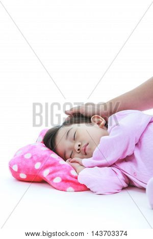 Healthy children concept. Adorable asian child sleeping peacefully. Adorable girl in pink pajamas sleep tight on floor isolated on white background. Mother put hand on daugyter's head lovingly.