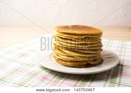 Stack of breakfast pancakes on the white plate. Homemade pancakes served for breakfast.