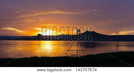 Tropical golden sunset on the Lake Taal Luzon Island Philippines. Horizon over the mountains and beautiful lake at sunset.