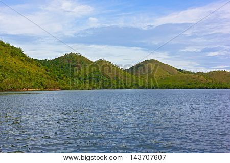 Beautiful sea and shore of Coron Island Philippines. Green hills with trees on the tropical island.