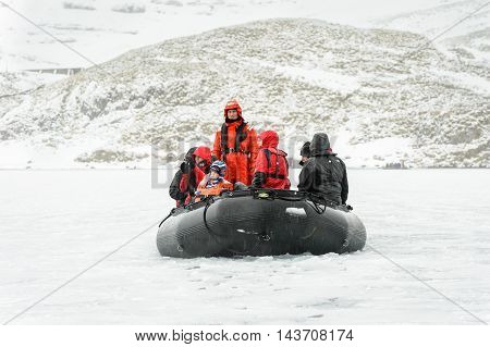 SOUTH GEORGIA, GREAT BRITAIN - NOV 9, 2012: Unidentified group of people and a child in a water proof suit in a rubber boat in the Atlantic Ocean. Atlantic Ocean is the world's second largest ocean