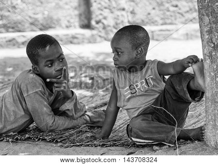 KARA, TOGO - MAR 9, 2013: Unidentified Togolese boys sit near a tree. Children in Togo suffer of poverty due to the unstable econimic situation