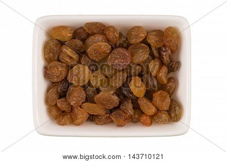 Bowl of brown raisins isolated on white background