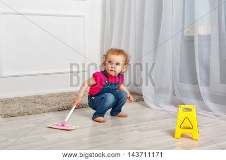 Little girl is cleaned with a mop in her hands. Little helper. Household chores.