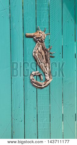 Wood driftwood seahorse decor on an aqua blue door in summer on Cape Cod