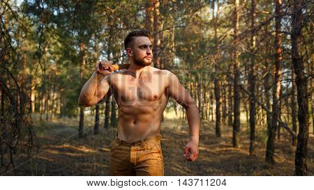 Lumberjack with ax goes through the woods. Woodcutter with a naked torso. Felling trees. Logging. Manual labor.