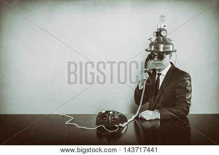 Vintage businessman sitting at office desk with phone
