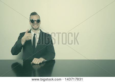 Businessman sitting at office showing ok sign