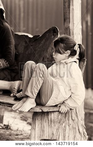 TA PHIN, VIETMAN - SEP 12, 2014: Unidentified girl sits on a wooden bench in the village of Vietnam. Red Dao is a minority ethnic group of Vietnam