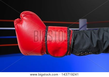 Hand Of Businessman In Suit With Red Boxing Glove In Ring.