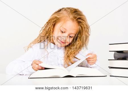Portrait of a beautiful little girl with a book. The child reads