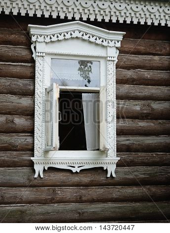 White open window with carved architraves of the old log house