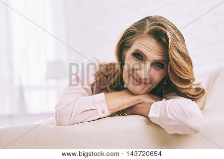 Face of cheerful mature woman resting indoors