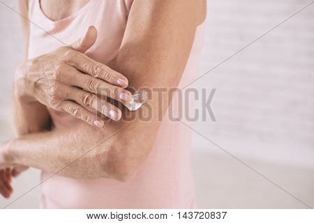 Woman applying body lotion to make skin softer