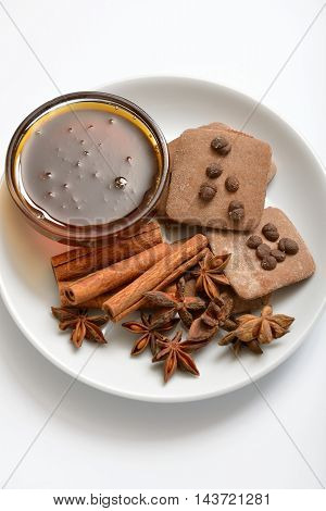 Cinnamon sticks anise stars and honey on a white plate