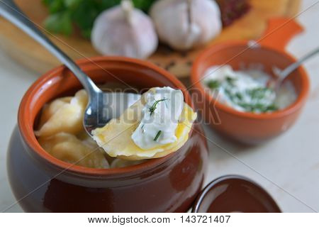 traditional Russian dumplings in ceramic pot with sour cream sauce